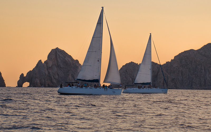 luxury sail boats at sunset in cabo|