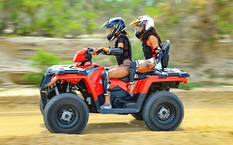 two cabo vacationers riding on an atv together|
