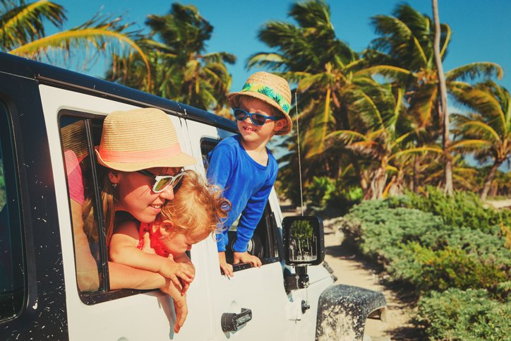 family driving off-road car on tropical cabo beach