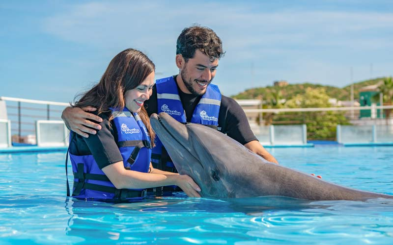 Couple hugging a dolphin in Cabo Adventures|