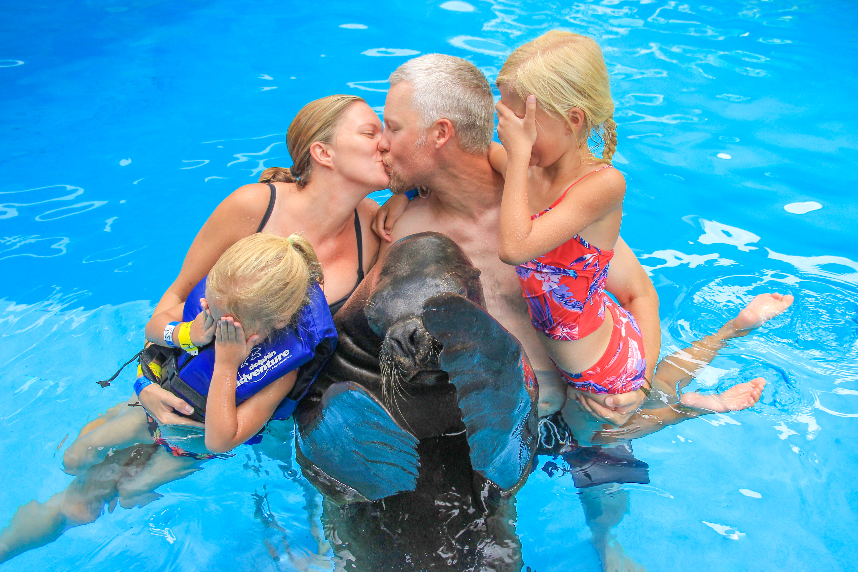 parents kissing while kids and sea lion cover their eyes