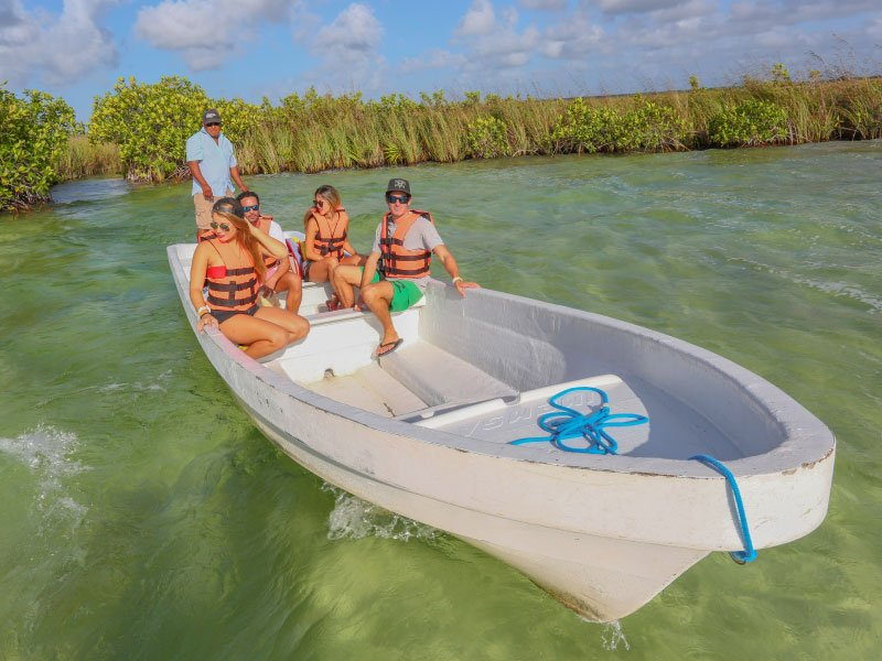 five people in a boat visiting cancun in the summer months