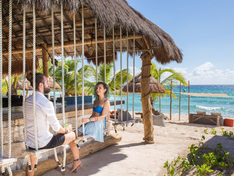 a man and a woman sitting on a cancun beach under a pavilion