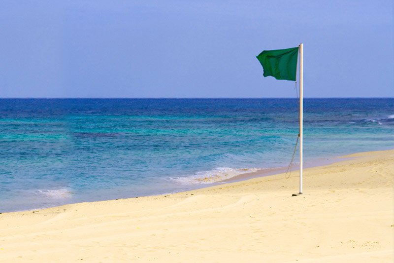 Green flag indicating a swimmable beach in Cabo