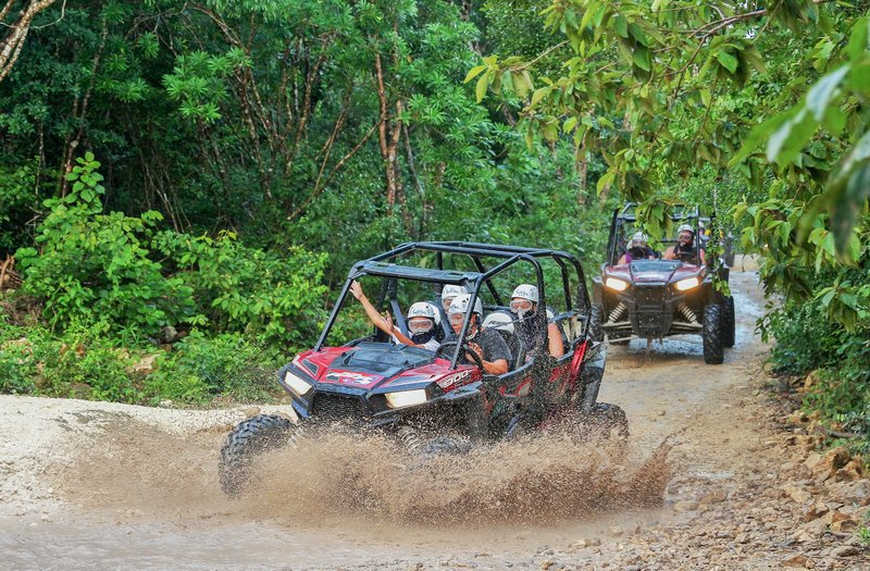 Group of people enjoying off roading in the mud