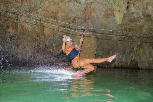 woman on a zip line in a cave