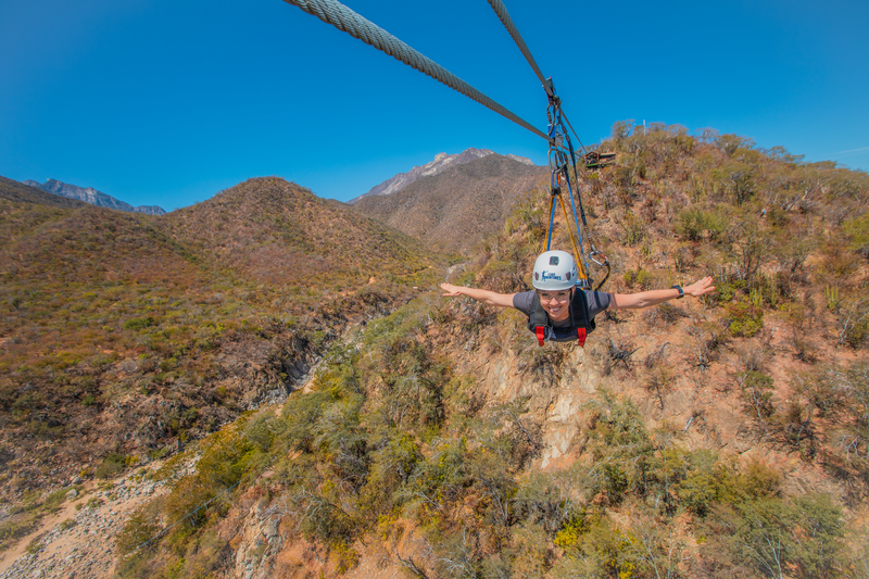 woman ziplining superman style in cabo