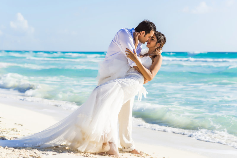 married couple kissing on beach