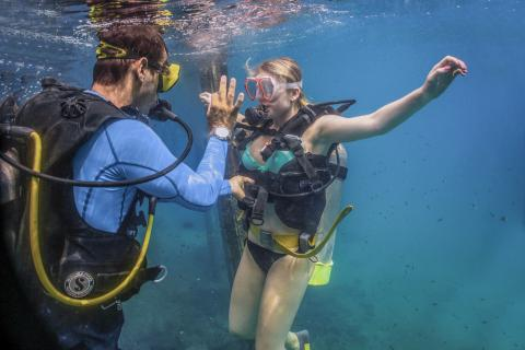 scuba diver instructor and scuba diving student underwater
