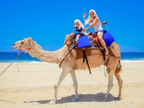 woman and young boy camel back riding